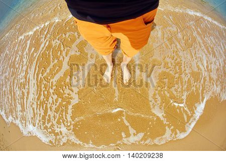 man in orange pants standing on the beach along the sea front. only legs in frame, view from top
