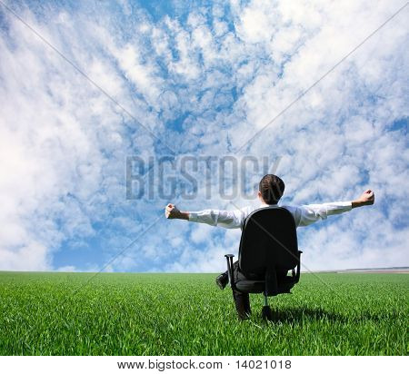 Man with raised hands sitting on chair on green meadow