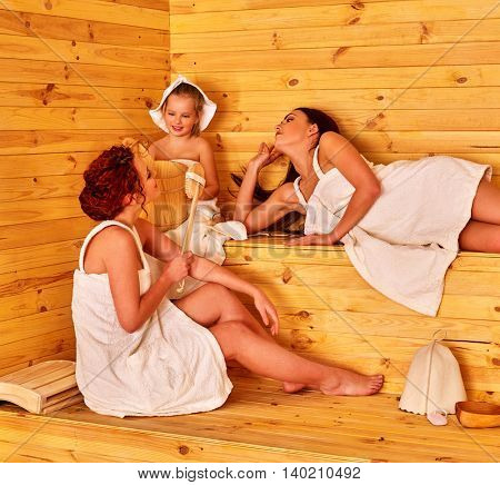 Group people with child in sauna. Women with child in sauna. Two mother with child girl have rest in sauna. Healthy lifestyle.