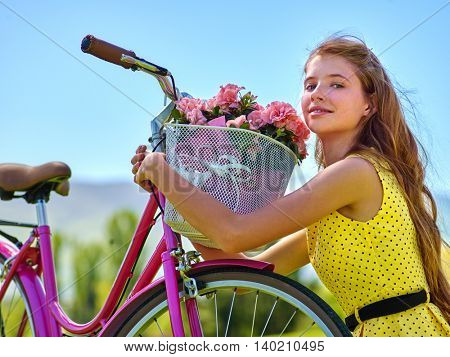 Teenager girl wearing yellow polka dots dress looking dreamily keeps bicycle with flowers basket. Lot of green tree and blu sky in park. Romantic style. Girl grabbed basket of flowers on bicycle .