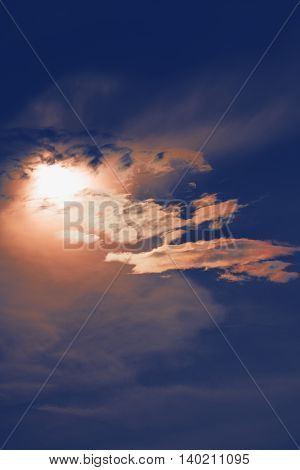 sunset with sun clouds over clouds. Spring scene. Dusk sky with sun hiding in clouds. Spring sunset