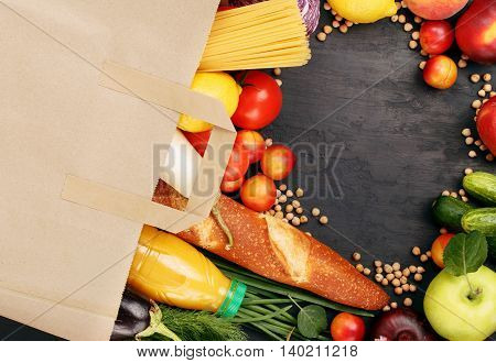 Paper bag with food on dark surface with copy space top view