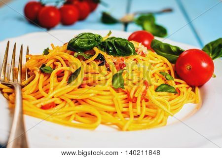 Traditional italian cuisine spaghetti with tomato sauce basil and cheese on blue table