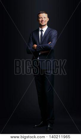 Handsome business man smiling on black background