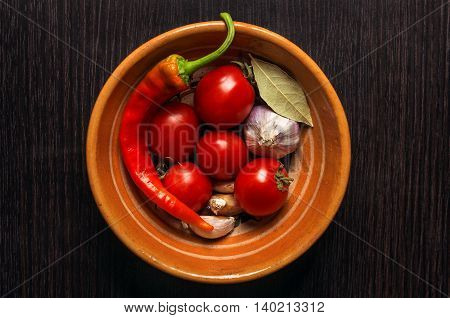 Composition with vegetables and spices in clay pot on black kitchen table