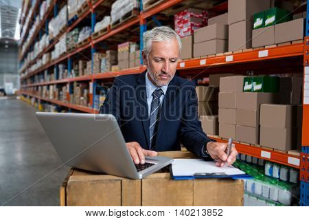 Business man concentrating during his work in a warehouse