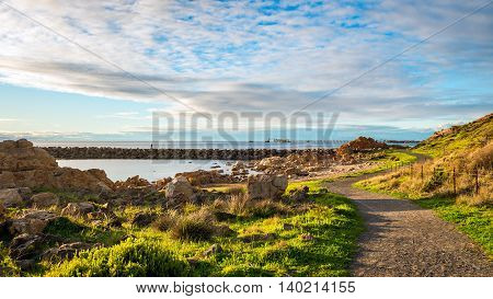 Footpath along the South Australian coast with fisherman silhoutte on the background at sunset