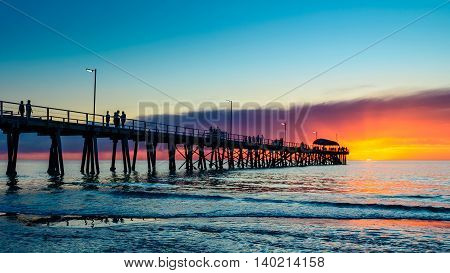 People relaxing on the Henley Beach Jetty at sunset South Australia. Color-toning effect applied