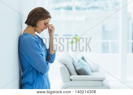 Side view of sad woman standing at home