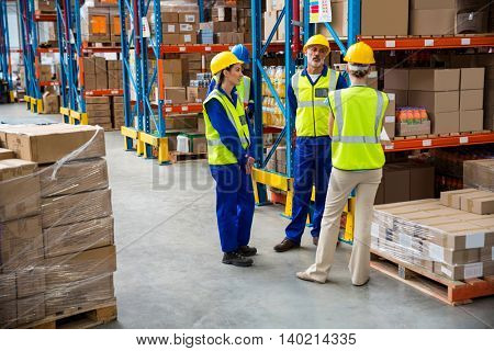 Workers speaking together in a warehouse