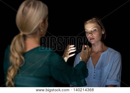 Hypnotist hypnotizing woman against black background