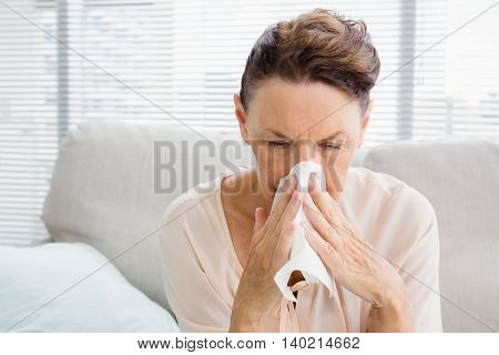 Mature woman with blowing nose while sitting on sofa at home