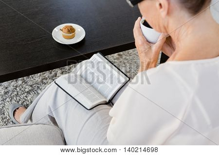 Rearview of mature woman reading book while sitting on sofa at home
