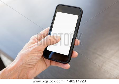 Cropped image of person holding mobile phone at table