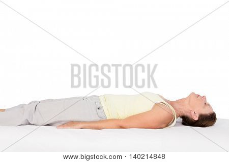 Side view of woman exercising on bed against white background