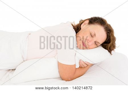 Mature woman hugging pillow while sleeping on bed against white background