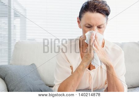 Mature woman suffering from cold while sitting on sofa at home