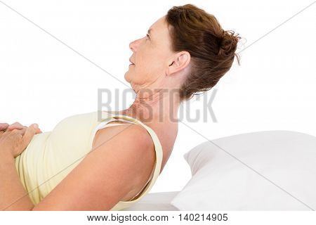 Mature woman exercising on bed against white background