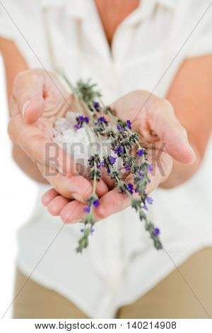 Midsection of woman holding flowers at spa