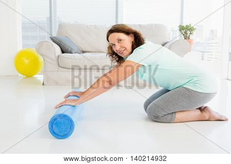 Portrait of smiling mature woman rolling exercise mat at home