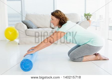 Full length of mature woman rolling exercise mat at home