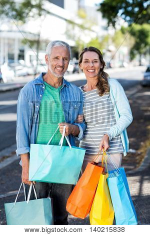 Portrait of mature couple holding shopping bags in city