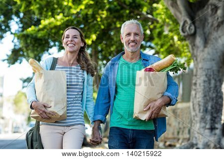 Happy mature couple holding shopping bags while walking by tree