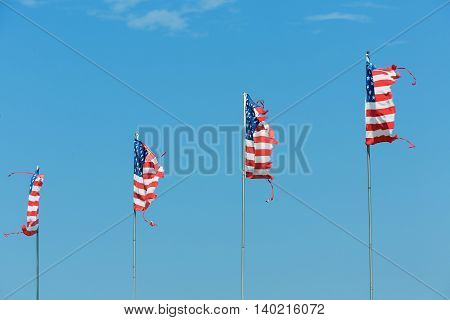 Four American flags blowing in the wind on blue sky