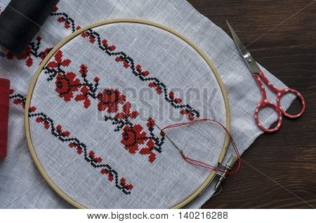 Hand embroidery cross-stitch flower ornament on a white fabric in the wooden embroidery hoop top view
