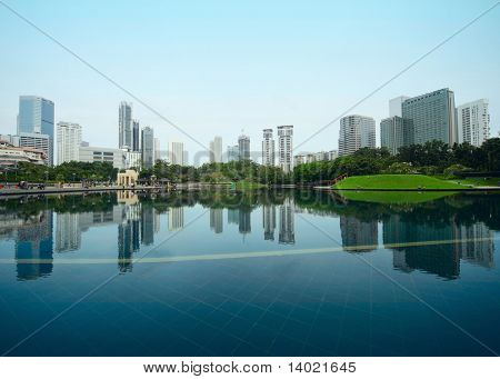 Buildings of a city with reflection in water. Kuala Lumpur