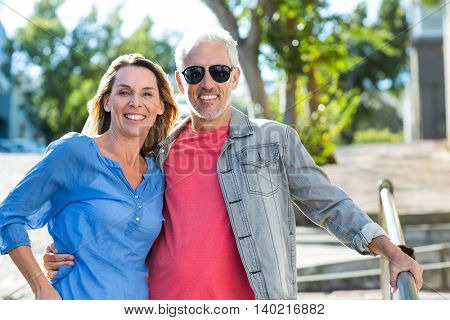 Portrait of happy mature couple standing on footpath in city