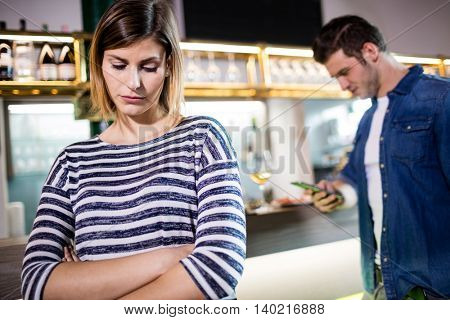 Upset woman with arms crossed while boyfriend using cellphone in background at bar