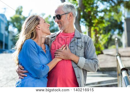 Romantic mature couple standing on footpath in city