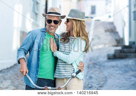 Smiling mature couple with bicycle standing on street amidst buildings