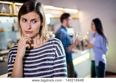 Upset woman with hand on chin while boyfriend talking with female friend in background