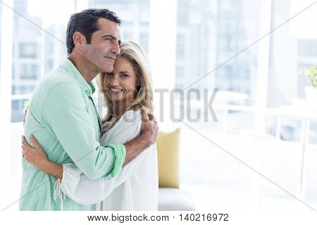 Mid adult romantic couple hugging at home