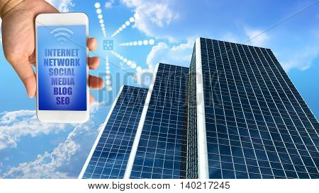 business building against beautiful blue sky and clouds with hand holding smartphone internet of things concept
