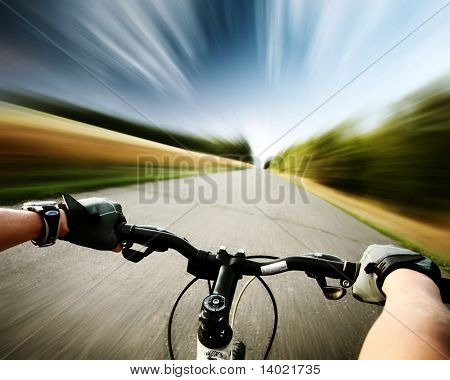 Rider driving bicycle on an asphalt road. Motion blurred background