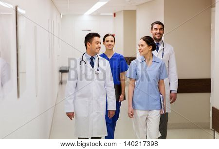 clinic, profession, people, healthcare and medicine concept - group of happy medics or doctors walking along hospital corridor