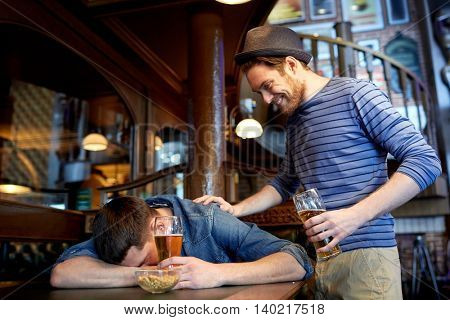 people, leisure, friendship and party concept - man with beer waking his drunk friend sleeping on table at bar or pub