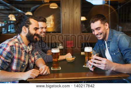 people, leisure, friendship, technology and bachelor party concept - happy male friends with smartphone drinking beer at bar or pub