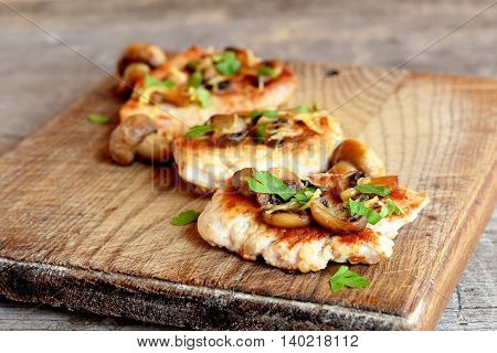 Roasted sliced Turkey breast with cheese, mushrooms and parsley on a cutting Board and an old wooden table. Delicious cooked Turkey meat. Lunch, dinner, picnic recipe. Closeup