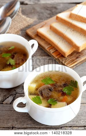 Vegetarian mushroom soup in bowls. Soup cooked of mushrooms, potatoes, carrots, parsley, salt, spices. White bread pieces on a chopping board, spoons on old wooden table. Delicious homemade food