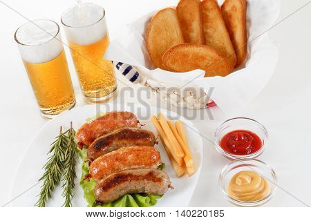 Oktoberfest traditional menu roast beef or chicken sausage on a plate with ketchup mustard and rosemary. White background