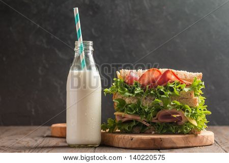 Club sandwich on a rustic table with milk
