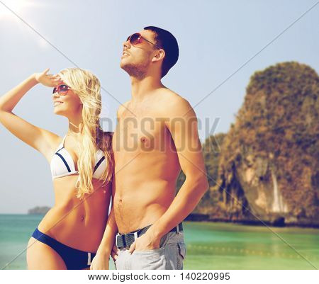 people, summer holidays, travel and vacation concept - happy couple over exotic tropical beach background