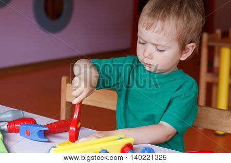kid child boy playing with toys tools in kindergarten