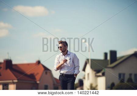 Cheerful young handsome man in glasses and looking away with smile while standing in city