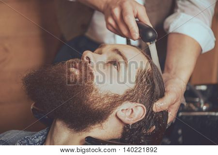 Hairstyling. Cropped image of barber washing head of his client in barber shop while preparing to haircut
