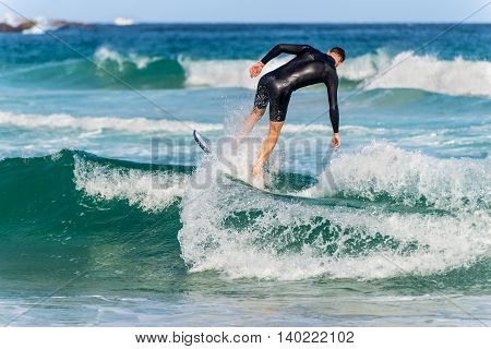 Sydney Australia - November 26 2014: A Australian surfer catching a wave Bondi Beach in the Eastern Suburbs Sydney New South Wales Australia.